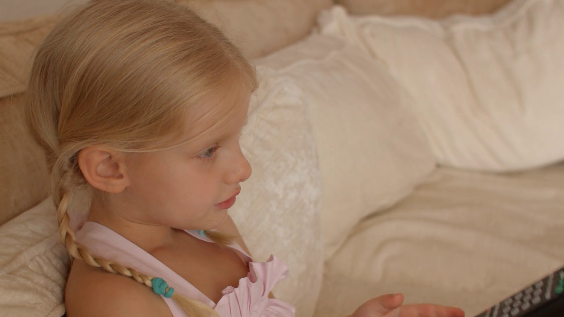 Little girl sitting on sofa with TV remote control Stock Video Footage - Storyblocks