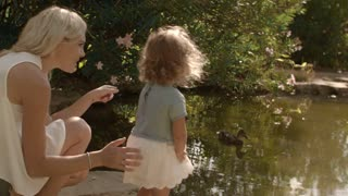 Mother and baby playing in park looking at ducks in pond