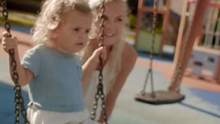 Mother and baby playing in park on swing