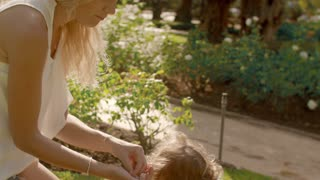 Mother and baby playing in park playing with flower petals