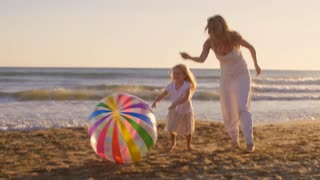 Mother and daughter running on beach with beachball