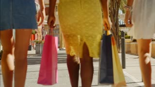 Three women walking away from camera with shopping bags in town
