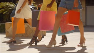 Three women walking with shopping bags in town legs only