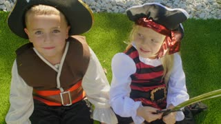 Two children in pirate costumes falling back onto ground playing dead