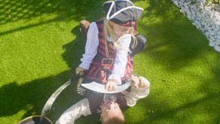 Two children in pirate costumes play fighting with toy swords