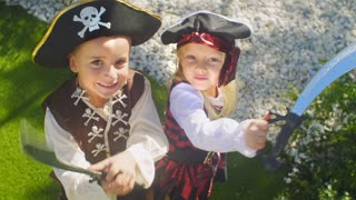 Two children in pirate costumes playing with toy swords