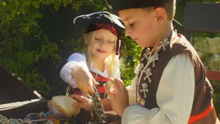 Two children in pirate costumes playing with treasure chest
