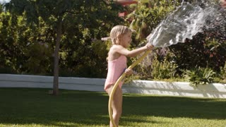 Two children playing with water hose in garden