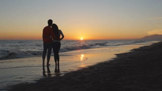 Young couple standing beach in sunset