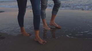 Young couple walking along beach away from camera in sunset