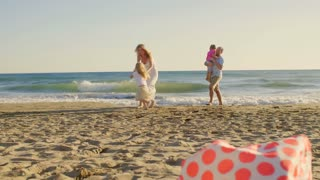 Young family on beach playing and twirling
