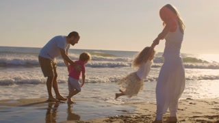 Young family playing and twirling on beach