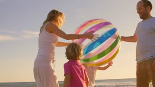 Young family playing with beachball on beach
