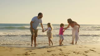 Young family running towards camera on beach