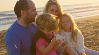 Young family sitting together on beach playing with sea shell
