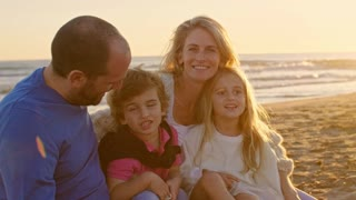 Young family sitting together on beach smiling at camera