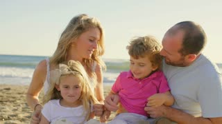 Young family sitting together on beach