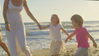 Young family walking and playing on beach