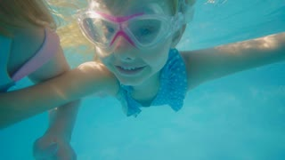 Young girl swimming underwater and smiling at camera
