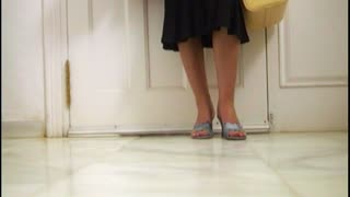 Woman arriving home, view of legs walking through door.