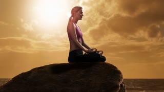 Woman doing yoga on rock beside ocean.