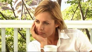 Woman drinking coffee on veranda looking bored
