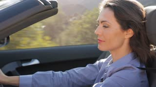 Woman driving convertible car in countryside.