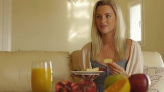 Woman eating breakfast on sofa.