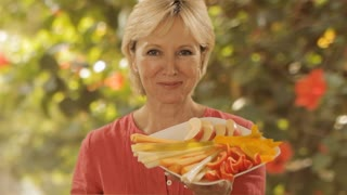 woman eating slice of carrot with garden background
