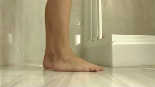 Woman entering shower, view of legs