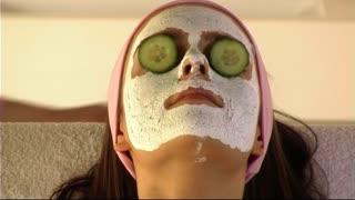 Woman having face mask beauty treatment