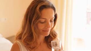 Woman in bedroom dinking glass of water