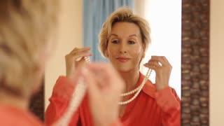 Woman in bedroom getting dressed in mirror putting on pearls.