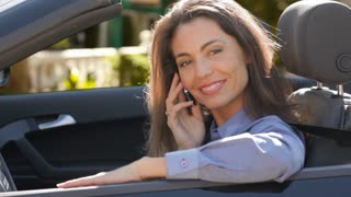 Woman in convertible car talking on cell phone.