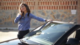 Woman leaning on car while talking on cell phone.