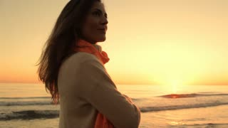 Woman looking at ocean in sunset.