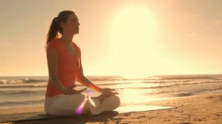 Woman meditating on beach in sunset.