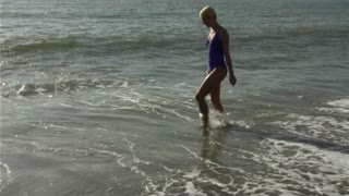 Woman on beach playing in surf