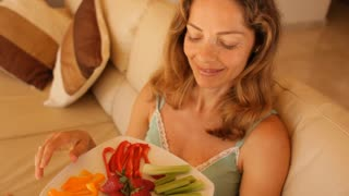 Woman on sofa eating fruit and vegetables