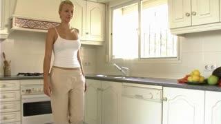 Woman preparing oranges in kitchen