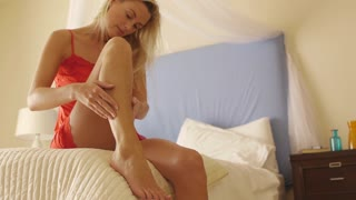 Woman putting cream on her leg in bedroom.