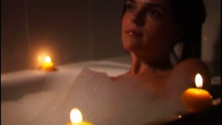 Woman relaxing in candle-lit bath