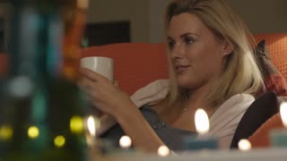 Woman relaxing on couch with drink.