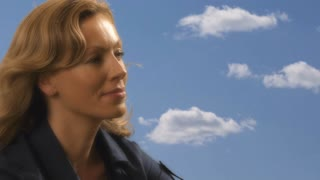 Woman relaxing outdoors with cloud background.