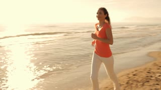 Woman running on beach in sunset.