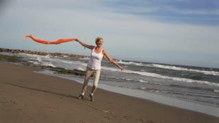 Woman running on beach with orange scarf.