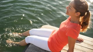 Woman sitting by lakeside with feet in water