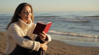 Woman sitting on beach reading book.