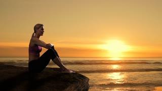 Woman sitting on rock beside ocean.