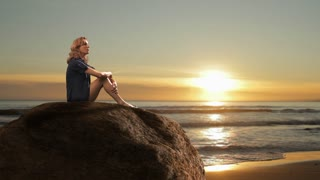 Woman sitting on rock on beach at sunset.